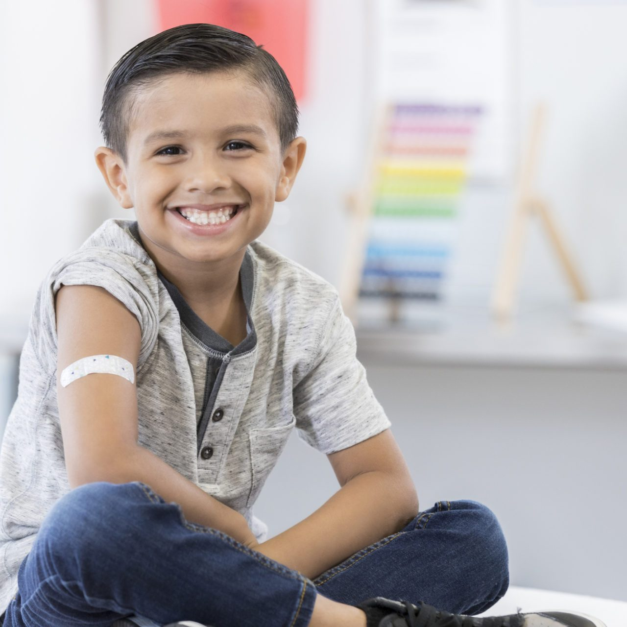 An adorable little elementary age boy sits cross legged on an exam table in his pediatrician's office.  He displays an arm bandage as he smiles for the camera.